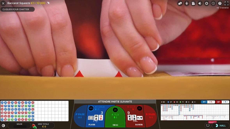 Zoom sur les mains de la croupière pliant les cartes de Baccarat Squeeze