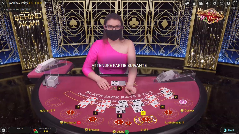 Croupière avec un masque à cause du Covid-19 sur la table Blackjack Party